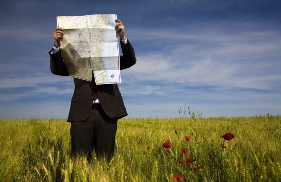 Man peers through a road map